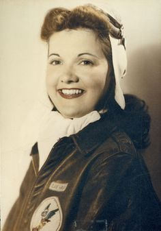 Portrait of Elaine Harmon, in 1944, in WASP A2 leather jacket with Fifinella patch and a flight helmet with goggles.