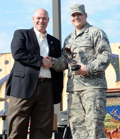 Mark Lear,USO VP of board of directors,presents Staff Sgt.Cody Foreman with USO Armed Forces Salute Award during free concert event,Whiteman AFB,Mo.,July 25,2014.Foreman's achievements in 2013 included coordinating multiple unit-wide field training exercises,revamping wing shelter program by identifying & correcting 103 issues preventing mission resiliency & devoting 120 hours to Habitat for Humanity,raising $10,000 to construct homes for local residents.(USAF Airman 1st Class Emili Koonce)