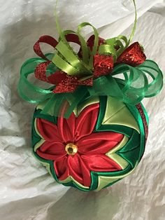 Beautiful ornament made with red satin for the flower. It is accented with kelly green and lt green for the leaves. It is topped with green and red ribbon. This ornament is very unique and a great gift idea for any teacher, hostess, or just because. PIN MY LISTINGS TO SAVE To get a
