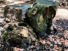 three handcarved lava rocks used as fountains. each is not necessarily taller than the other, other large rocks are used underneath to support and/or heighten them.