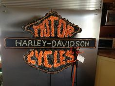 Harley Davidson Funeral flower sign. We made this recently for a customer. The majority of the sign was filled in with carnations. To add detail, we outlined it with creative coils, and wrote out the word Harley Davidson with tiny little way flowers held in place with pearl pins. www.TheLoftFlorist.com