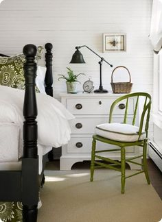 White and green bedroom with black painted bed.