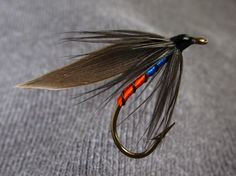 Harlequin - Body, half orange floss half blue, Rib, black floss, Hackle, black, Wing, dark slate.