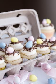 A carton of white chocolate Easter egg cupcakes > a carton of eggs