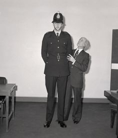 The image is simply captioned 'Force's Tallest PC' and comes from the 1976 section of the archives of the Greater Manchester Police Museum. We do not know the identity of the officer or the man glancing, somewhat pensively, up at him. We assume he was new to the Force at the time and that the image may have been take for publicity purposes. Does anybody remember this officer? Exactly how tall was he? www.gmpmuseum.co.uk