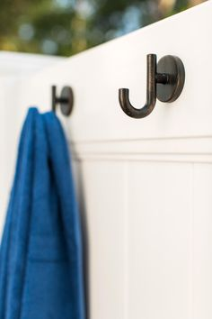 Aged bronze hooks, a material similar to others used inside the home, are attached to the inside wall of the outdoor shower to hold towels.