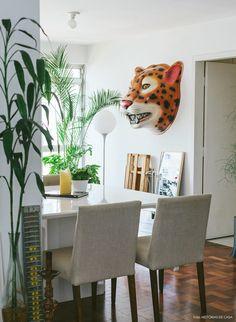 Sala de jantar com muitas plantas e decoração com pegada kitsch.