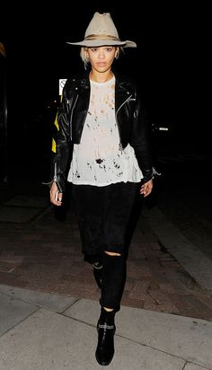 Rita Ora wears a cropped leather moto jacket, hat, ripped top and jeans, and booties.