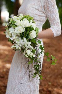 Gorgeous trailing wedding bouquet of White Roses, White Dendrobium Orchids, Green Hydrangea and assorted foliage and vines.