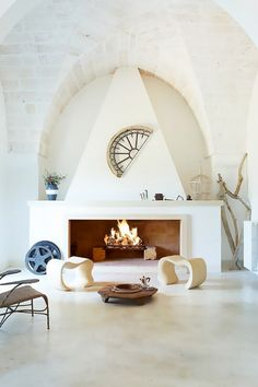 All-white living space with a stone fireplace as the focal point of the living room