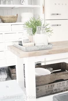 Table pietement blanc, plateau bois naturel ; frigo Smeg blanc