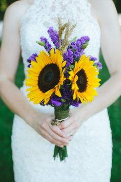 """Remembrance Wedding Bouquet made by the Bride to honor the deceased: sunflowers to represent her dad and sister; 6 wheat heads for her 4 grandparents and 2 of the groom's grandparents, along with the wedding rings of her dad and two grandmothers. Purple lisianthus and statice for friends and family both near and far as the """"cloud of witnesses"""" (Hebrews 12:1), with a few buds for those yet to come."""