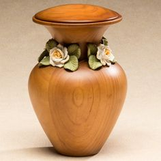 The Tranquility Wood Cremation Urn is work of art, crafted from Radiata Pine wood in the shape of a vase and surrounded by handmade ceramic white roses.