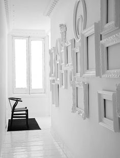 The absence of art.  This groupings of simple white lacquered frames just adds dimension and curiosity to a simple white wall.  cool.