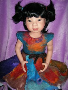 Beautiful Mulan......hand painted vinyl doll ...delicate eyelashes frame pretty eyes....delicate veining can be seen on the limbs....many layers of fine painting to achieve skin tones...  Australian merino crafted into fine felted fabric and then hand made into a cute little dress and trimmed with blue glass beads.......have a cuddle up at Maleny Marketplace where she is for sale.........