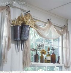 WINDOW TREATMENTS: Unique, Scrim (a net like fabric) valance, old coat hooks serve as drape points for scarf valance, copper funeral urns on left filled with cornhusk, brown colored bottles on window sill