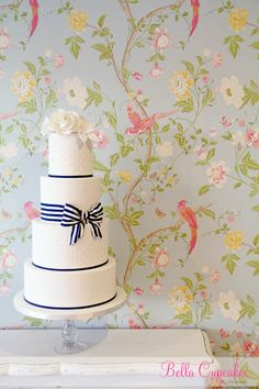 Navy Blue & White! Fondant covered with hand pipped royal icing dots.  Fondant stripe ribbon bow and gumpaste handmade roses.