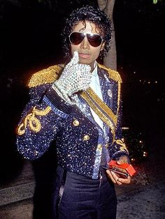 Michael Jackson wearing a military jacket covered in glitter with massive shoulder pads. <3