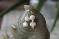 Hi, I made this nice earring with:  White freshwater pearl beads.  Sterling french hoops. The earrings is about 1.5 long and comes with stoppers to prevent earring loss.  If you have any question, feel free to contact me. Thanks for looking and have a good one