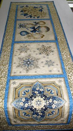 Christmas Table Runner, elegant, handmade, quilted, fabric from Kaufman Flourish Line Measures 46.5 x 15.25 inches Made by Chris This gorgeous fabric has beautiful brilliant silver and gold metallic with the most gorgeous ornaments, poinsettias, medallion and blue snowflakes etched