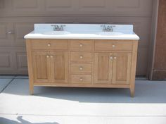 Shaker style cherry tall bath vanity with a 2 sink top. The cabinet has 4 centrally located drawers. There are 2 false drawer fronts and double doors on either side of the drawer stack. The doors and drawers are flush mounted and use a beading detail to accent the openings. Approximate cost $450.