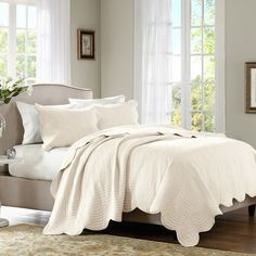 Add a touch of texture to your master suite or guest bedroom decor with this chic coverlet set, showcasing scalloped edges and an embroidered design.