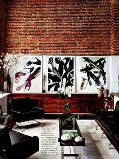 Sala de estar com revestimento de tijolos a vista e quadros decorativos