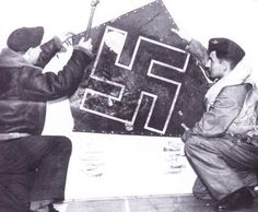 """Sgt Josef Stehlík (left) and P/O Alois Vašátko hang up the swastika panel from the tailfin of the Bromborough 88 inside the dispersal hut of No 312 Squadron RAF at RAF Speke, shortly after the Ju 88 was intercepted on 8 October 1940. The souvenir was removed by F/L Denys E """"Kill 'em"""" Gillam, before the bomber was placed on display at the Oval Recreation Ground, helping to collect over £70 for the Mayor of Bebington's Spitfire Fund."""