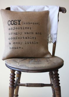 cosy, sungly warm and comfortable a cosy little house,pillow, wood chair, words, quote.