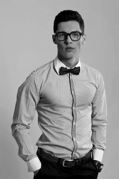 man wearing a shirt too tight for his pectorals, rouge on his cheeks, hipster glasses....oh, and a bowtie.