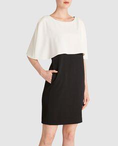 Vestido corto, con cuerpo tipo capa en color blanco y falda negra, de tipo recto y dos bolsillos laterales.