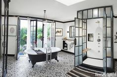 Designer Deirdre Doherty gives a fresh look to this bathroom in an old Spanish Revival house. By blending in a bit of industrial chic, the space feels totally new. Drummonds' Spey tub and standpipe take center stage, but the glass-and-steel shower stall, fabricated by Elite Remodeling, is equally eye-catching. Wall tile, Michael S. Smith for Ann Sacks. Floor tile, Cluny by Granada Tile. Tub shelf, Etsy. Rug, Woven Accents. Vintage pendant, Obsolete. Ceiling paint, Dunn-Edwards Suprema in…