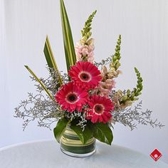 Gerbers with snapdragons - nice use of tropical leaves and limonium