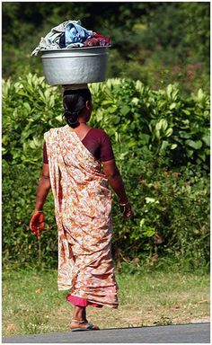 """India -- carrying the laundry to the river to be washed by hand. These women may not have paid jobs, but no one ever better say they """"don't work"""" -- in most countries, women work harder than anyone!"""