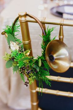 Elegant greenery and a brass horn dress up this table