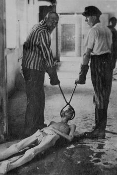 Survivors of the Dachau concentration camp demonstrate the operation of the crematorium by dragging a corpse toward one of the ovens. Dachau, Germany, April 29-May 10, 1945.