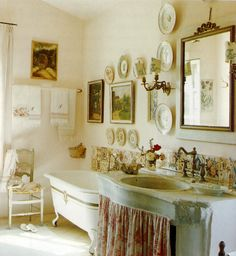 cottage bathroom is filled with plates, a clawfoot tub, old framed prints, an antique chair, and a skirted sink - love all of it. Ivy House, Victorian Bathroom, Vintage Bathrooms, Dream Bathrooms, Beautiful Bathrooms, Romantic Bathrooms, Vintage Tub, Vintage Houses, Chic Bathrooms