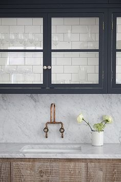 kitchen renovation inspiration - navy blue exposed cabinets with brass hardware and marble countertops