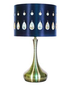 This table lamp features an array of nearly 40 hand-strung jewels set against a darkly hued shade. The crisp metallic sheen of the base complements and completes the look.