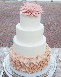 Se você gosta de contraste e um bom babado chamativo, este ruffled cake vai te agradar mais. Para não ficar demais, a textura foi aplicada apenas na base do bolo de casamento, deixando as camadas superiores lisas. A flor em tonalidade pastel complementa a tonalidade da textura da base, fechando este bolo de casamento com delicadeza e harmonia. Mais fotos de bolos de casamento? Vem engordar com a gente neste post!