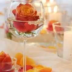 "Using long-stemmed wine glasses, put a little water in the glass and float the head of a flower. Also, add some beads or marbles to make it ""pop"". Beautiful centerpiece idea!"