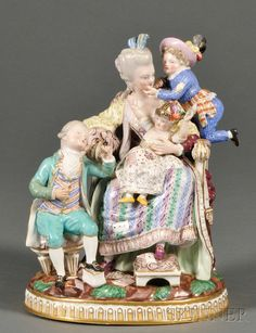 Meissen Porcelain Figural Group, Germany, 19th century, gilded and polychrome enamel decorated, modeled as a mother seated in an armchair with a child on her lap, another at her shoulder, and one by her side seated on a stool.