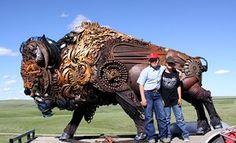 Tourists pose by a John Lopez sculpture