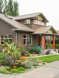 A fun and bold choice for a Craftsman Bungalow. Love the bright orange vs. a traditional brick red paint color on the window trim and columns with the taupe siding and metal roof. Lime green adds an extra pop of interest.