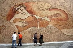 """Romeo with a crown of grapes playing the guitar while dancing with the sea and the sun"" (Massive, world-record wine cork mosaic by Saimir Strati)"