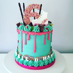 Joint 6 year old boy and girl roller skating party drippy cake. 4 layers of pink and turquoise cake, covered with turquoise buttercream and bright pink White chocolate ganache drip. Topped with all sorts or treats.
