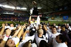 Bellevue's Conner Lamear raises the Class 3A championship trophy as his teammates surround him following their dominating win over Eastside Catholic, 35-3. (Photo by Colin Diltz / The Seattle Times)