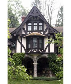 The half-timbered gable of a Tudor Revival house incorporates many architectural elements, including a bay window, a row of three windows with arched transoms, and a timber bargeboard (decorative gable trim) Storybook Homes, Storybook Cottage, Tudor Cottage, Cottage Homes, Casas Tudor, Casa Estilo Tudor, English Tudor Homes, Tudor Style Homes, Victorian Terrace