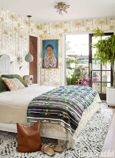 """Don't overlook a DIY project.Justina Blakeney designed the curvy headboard with built-in nightstands for her """"Jungalow"""". The bed is dressed in a Matteo duvet cover and a vintage Moroccan wedding blanket. The rug is by Blakeney for Loloi. The ceramic pendant lamp and artwork are vintage."""