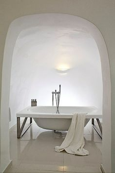 Stark contrast between the organic room and the modern tub and floor